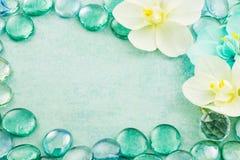 Błękitny szkło opuszcza aqua z białych kwiatów orchidei tłem Fotografia Royalty Free