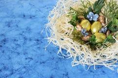 Złoci czekoladowi jajka w gniazdeczku Obraz Royalty Free
