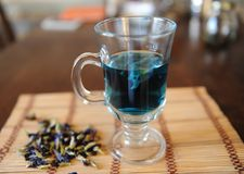 Błękitny Tajlandzki herbaciany anchan w szklanej filiżance na bambus macie na drewnianym stole Placer kwiaty clitoria obok filiża Fotografia Royalty Free