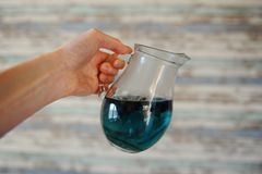 Błękitny Tajlandzki herbaciany anchan w szklanym dzbanku w szeroko rozpościerać ręce na lekkim drewnianym pasiastym tle Fotografia Royalty Free