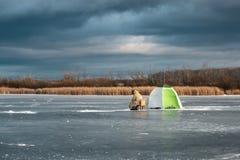 Błękitny tragiczny niebo lód na stawie i rybaku siedzi blisko szalika, zima okres Fotografia Stock