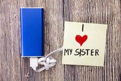 błękitny władza bank ładuje z białym dane kablem utrzymującym i pisać na stronie na drewno stole ogromnie kocham mój siostry któr obraz stock