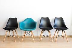 Błękitny wygodny krzesło wśród czerni obraz stock