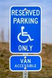 Błękitny Zarezewowany Parking Van Dostępny znak z mężczyzną na wózek inwalidzki ikonie fotografia royalty free