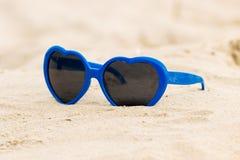 Błękitnych okularów przeciwsłonecznych kształtny serce na piasku Fotografia Stock
