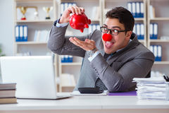 Błazenu biznesmen z prosiątko bankiem robi księgowości Fotografia Stock
