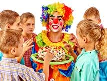 Błazenu mienia tort na urodziny z grupowymi dziećmi Fotografia Royalty Free
