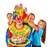 Błazenu mienia tort na urodziny z grupowymi dziećmi Zdjęcia Stock