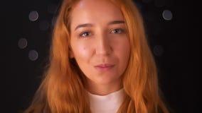 Błogi materiał filmowy zamknięty w górę caucasian rudzielec kobiety pozycji i patrzeć kamerę z naturalnym uśmiechem i otwartym wi