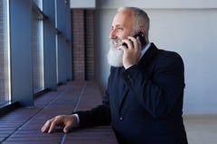 Błogi sir opowiada na telefonie podczas gdy opierający na parapecie Zdjęcie Stock