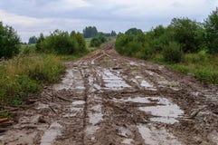 Błotnista droga gruntowa w górkowatej wsi Obraz Royalty Free