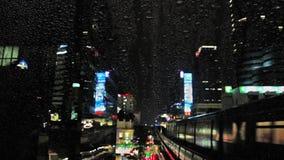Błyskawica i deszcz w centrum Bangkok z ruchem drogowym, samochodami i pociągiem, przy nocą, widok przez okno z kroplami deszcz zbiory