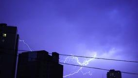 Błyskawica w nocnym niebie w mieście, jaskrawy błysk światło w chmurach w deszczu, burza zbiory