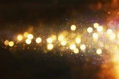 Błyskotliwość rocznik zaświeca tło czarne złoto defocused obrazy royalty free