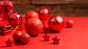 Błyszczące nowożytne boże narodzenie dekoracje kłama na czerwień stole przed starą drewnianą ścianą zdjęcia royalty free