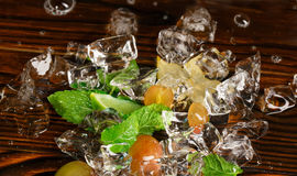 Błyszczące zimne kostki lodu Zamraża z żółtymi jagodami, wapno segmentami, carambola i mennic gałązkami, Składniki dla lato kokta Zdjęcie Royalty Free