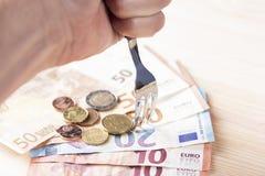 B?yszcz?cy metalu rozwidlenie przebija stos euro banknoty i monety na drewnianym stole zdjęcie royalty free