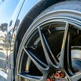 Błyszczący samochód z czarnym mag kołem i czerwonymi lug dokrętkami obrazy stock