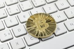 Błyszczący złocisty Bitcoin menniczy kłaść na białej klawiaturze Zdjęcia Stock