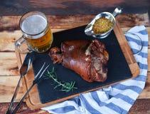 b被烘烤的猪肉小腿、迷迭香分支和蜂蜜sause和玻璃  免版税图库摄影