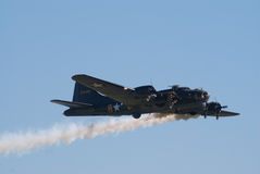 B-17 Flying Fortress with smoke trail Royalty Free Stock Image
