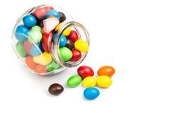 透明玻璃瓶子用在白色b的五颜六色的巧克力糖 免版税库存图片