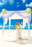 在一个热带海滩的婚礼在白色 愉快的新郎和b 免版税图库摄影