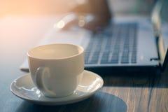 杯热奶咖啡咖啡与膝上型计算机在桌上,咖啡店b的 免版税库存照片