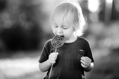 B;ack and white photo of cute toddler boy with big lollipop Royalty Free Stock Photo