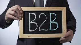 B2B affär-till-affär regel som är skriftlig på svart tavla, hållande tecken för man, försäljningar stock video
