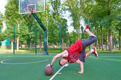 B-boy doing stunt trick on basketball field with ball. B-boy doing stunt trick on basketball playground with ball Royalty Free Stock Photography