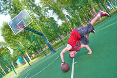 B-boy doing stunt trick on basketball field with ball. B-boy doing stunt trick on basketball playground with ball Royalty Free Stock Images