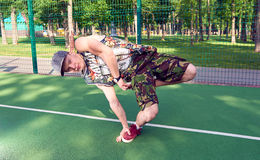 B-boy doing stunt trick on basketball field with ball. B-boy doing stunt trick on basketball playground with ball Royalty Free Stock Image