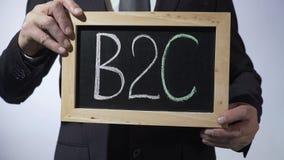 B2C affär-till-konsument som är skriftlig på svart tavla, hållande tecken för affärsman stock video