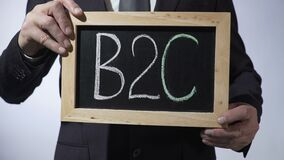 B2C, business-to-consumer written on blackboard, businessman holding sign. Stock footage stock video