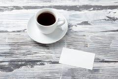 B-cartões vazios da foto com xícara de café em uma textura de madeira Copie o espaço para seu anúncio Fotografia de Stock