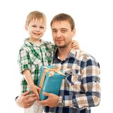 1b84cd84-b71e-4Happy son hugging his father and gives him gifte23-9694-1a71fe72f296. Happy son hugging his father and gives him gift. Fathers day, family holiday stock image
