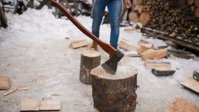 Bûcheron coupant le bois avec une hache dans la neige banque de vidéos