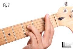 B flat dominant seventh guitar chord tutorial. Bb7 - dominant 7th keys guitar tutorial series. Closeup of hand playing B flat dominant seventh chord on guitar Royalty Free Stock Image
