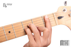B flat minor guitar chord tutorial. Bbm - basic minor keys guitar tutorial series. Closeup of hand playing B flat minor chord on guitar, isolated on white Stock Image