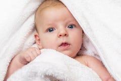 B?b? heureux avec une serviette apr?s la douche dans le lit ? la maison Un bébé nouveau-né nouvellement baigné dans une serviette photos libres de droits