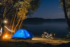 B??kitny Campingowy namiot Iluminuj?cy W?rodku Nocy godzin Campsite odtwarzanie Motocyklu podr??nik, turystyczni rowerzy?ci jezio zdjęcie royalty free