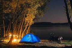 B??kitny Campingowy namiot Iluminuj?cy W?rodku Nocy godzin Campsite odtwarzanie Motocyklu podr??nik, turystyczni rowerzy?ci jezio zdjęcia stock