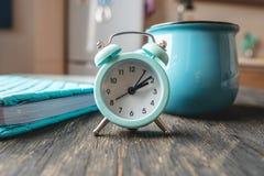 B??kitny metalu budzik na stole z kubkiem i dzienniczkiem na tle kuchnia Czas i domowy tryb obrazy stock