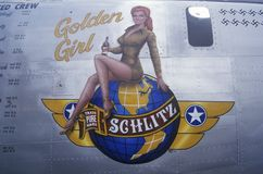 A B24 Liberator bomber is decorated with the Schlitz Golden Girl logo and swastika marks for the number of German planes downed du Royalty Free Stock Photos