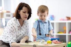 B?b? mignon d'enfant en bas ?ge jouant avec le busyboard Enfant d'enseignement de m?re ou de babysitter dans la cr?che Jouets ?du images stock