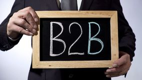 B2B, règle d'entreprise à entreprise écrite sur le tableau noir, homme tenant le signe, ventes Image stock