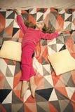B?r den lilla ungen f?r flickan mjuk gullig pyjamas, medan koppla av p? s?ng Tr?ttat behandla som ett barn att koppla av Pyjamas  arkivfoto