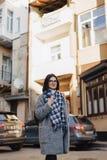 B?rande exponeringsglas f?r attraktiv positiv ung flicka i ett lag p? bakgrunden av byggnader p? bilar fotografering för bildbyråer