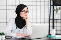 B?rande hijab f?r mellersta h?g arabisk sjuksk?terskakvinna f?r ?lder p? det medicinska kontoret med handen p? hakan som t?nker o arkivfoton